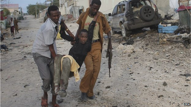 An injured man is evacuated from a scene of a car bomb explosion in front of a hotel in Mogadishu, Somalia, 27 March 2015