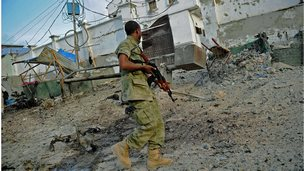 A solder walks past at the scene of a car bomb attack and armed raid by Al Shebab militants on the Maka al Mukarama hotel in Mogadishu on March 27, 2015