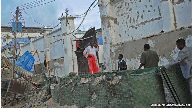 An injured man gestures at the scene of a car bomb attack and armed raid by militants on the Maka al Mukarama hotel in Mogadishu on March 27, 2015.