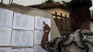 A volunteer checks her ballot station position in the Bayelsa state capital of Yenagoa on 27 March