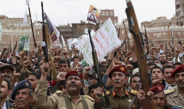 Houthi rebels hold up their weapons to protest against Saudi-led airstrikes, during a rally in Sanaa, Yemen, 26 March 2015