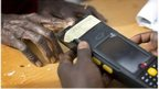 Nigerian woman validating her voting card by using a fingerprint reader; 28 March 2015