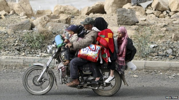 A man flees with his family and their belongings on a motorcycle in Sanaa March 28, 2015