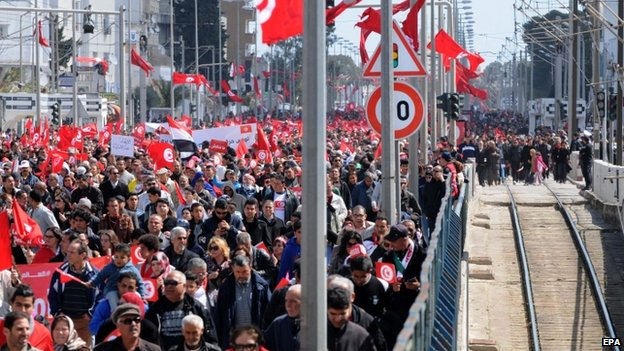 Tunisian people wave the national flag during a march to denounce terrorism, in Tunis, Tunisia, 29 March 2015.