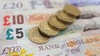 Pound coins on top of bank of England banknotes