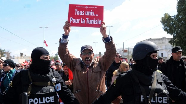 """Tunisian soldiers guard as a protester holds a placard reading """"all united for Tunisia"""" during a march to denounce terrorism, in Tunis, Tunisia, 29 March 2015"""