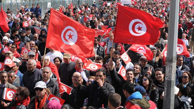 Tunisians waving flags march in the capital Tunis in a protest against extreme violence