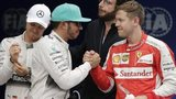 Lewis Hamilton shakes hands with Sebastian Vettel as Nico Rosberg waits to congratulate the German