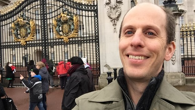 BBC reporter Anthony Zurcher stands outside Buckingham Palace.