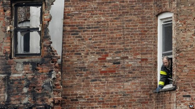 A fire official stands at the window of a building adjacent to the site of a building collapse in the East Village neighborhood of New York, Friday, March 27, 2015
