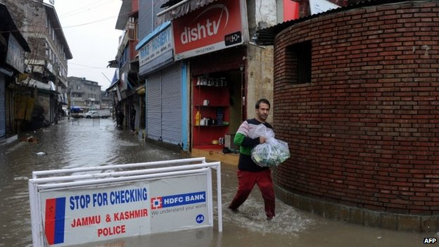 A shopkeeper carries goods down a flooded road in Srinagar after heavy rainfall on March 29, 2015