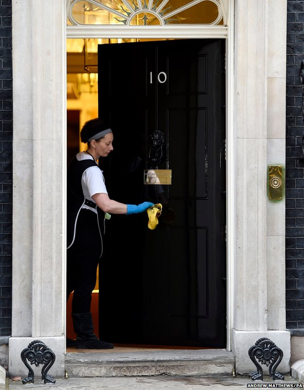 A cleaner polishes the handle of 10 Downing Street