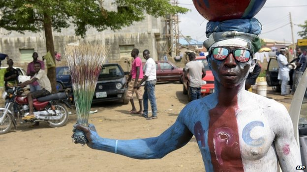 A man wears glasses and body paint adorned with the logo of Nigeria's main opposition All Progressives Congress (APC) as residents await results of the presidential election in Abuja