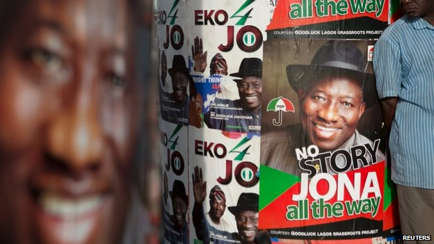 A man stands in front of electoral campaign posters in Lagos March 30, 2015