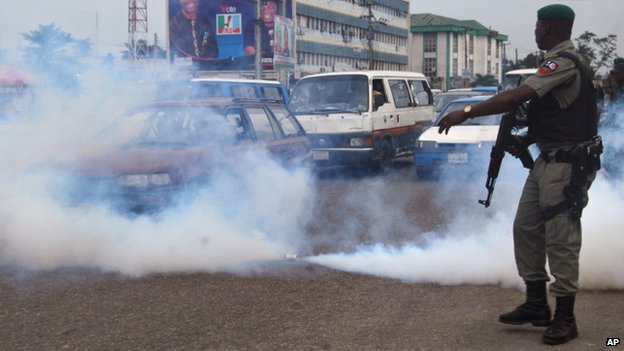 A Nigerian soldier stands next to a tear gas canister as it sprays gas into traffic during a protest by members of the All Progressives Congress