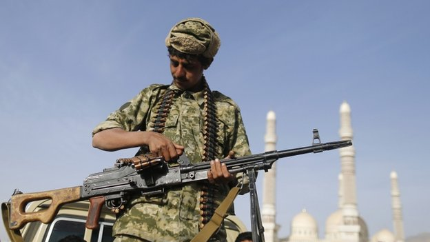 A Houthi fighter holds a machine gun as he rides a truck near the Presidential Palace in Sanaa