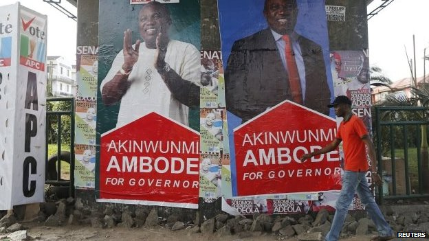 A man walks past banners campaigning for All Progressives Congress (APC) governorship candidate Akinwunmi Ambode, under a bridge in Lagos April 6, 2015