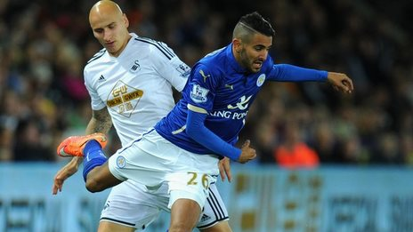 Swansea's Jonjo Shelvey tussles with Leicester's Riyad Mahrez