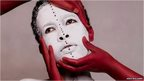 Photograph by Aida Muluneh of an African woman, her face painted white face and being held by three hands, painted red