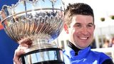 Jockey Robbie Dunne shows off his huge prize after clinching victory in the Scottish Grand National