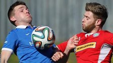 Linfield's Stephen Lowry competes against Cliftonville's James Knowles