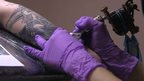 arm being tattooed