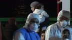 Rescuers and migrants arrive in Sicily
