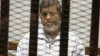 "Egypt""s ousted Islamist President Mohammed Morsi sits in a defendant cage in the Police Academy courthouse in Cairo, Egypt"