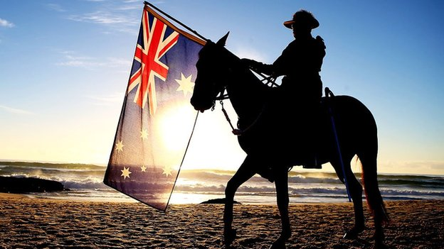 A soldier on a horse holding the Australian flag on a beach