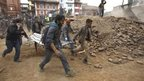 People carry the body of a quake victim in Kathmandu (25 April 2015)