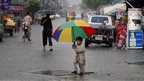 A young boy holds a bright umbrella as he crosses the road during heavy rain