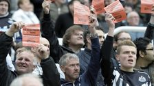 Newcastle United fans hold up signs