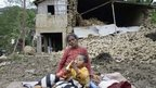 Earthquake victims in front of a destroyed house in Nepal, 27 April 2015