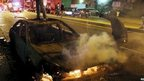 A rioter stands atop a burning car