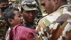 An boy injured in the earthquake cries in pain as he is carried by Nepal Army personnel to a helicopter on Monday