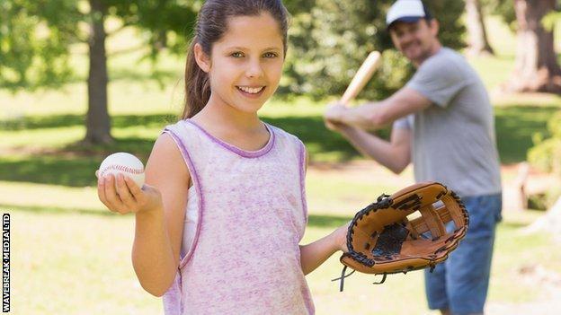 girl holding baseball and glove