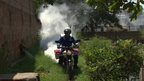 A motorbike with insecticide being sprayed from the back