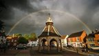 A rainbow arches over a market square. The sky is dark and cloudy