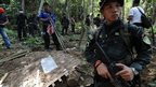 Soldiers stand guard as rescue workers and forensic officials dig out skeletons from shallow graves covered by bamboo at the site of a mass grave at an abandoned jungle camp in the Sadao district of Thailand's southern Songkhla province bordering Malaysia on May 2, 2015