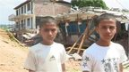 Brothers Ganesh and Santos Bharati standing in front of the remains of their school