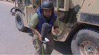 Omar Abdel-Razek next to armoured vehicle