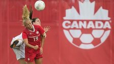 Canada's Adrianna Leon (front) and England's Claire Rafferty compete for the ball in Hamilton