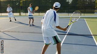 teenage boys playing tennis outdoors