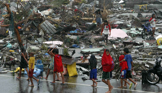 Survivors walking past debris of flattened homes