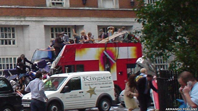 Image of a number of people, some standing on the wreckage of a bus, other standing nearby.