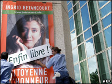 """A poster in France of Ingrid Betancourt is covered over with a sign """"Free at last"""""""