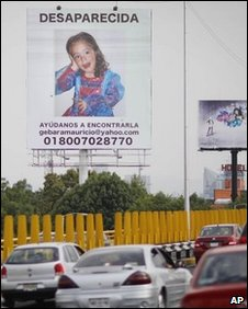 Vehicles pass a billboard with a photo of Paulette bearing an appeal to help find her