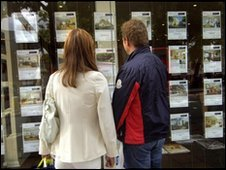 Two people look in an estate agent's window