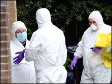 Forensic scientists examine the scene where Mr Cunningham was killed