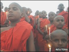 Buddhist monks attend a candlelight prayer ceremony for the victims of the crashed Air India Express passenger plane, in the central Indian city of Bhopal